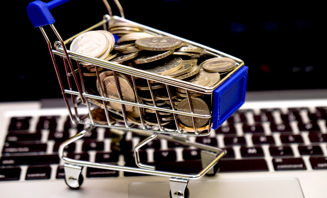 Shopping trolley full of coins on laptop - Turn your web visitors into buyers with web analytics