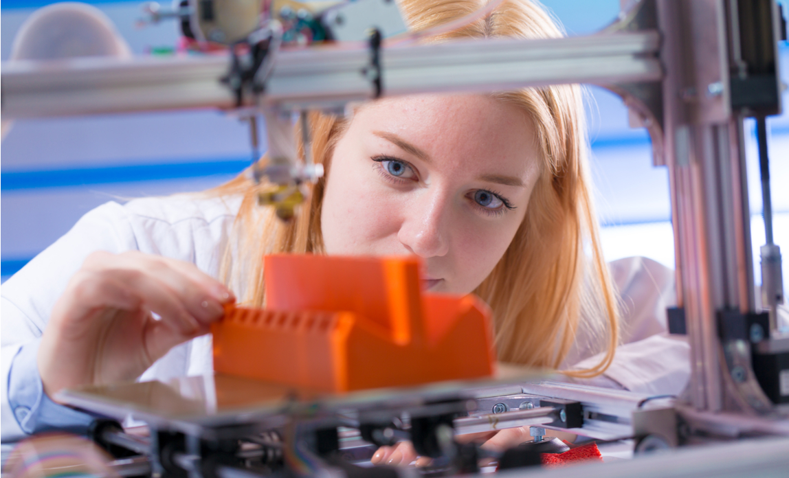 A factory employee works with a 3D printer to manufacture components.