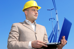 Man wearing hard hat on building site holding a laptop