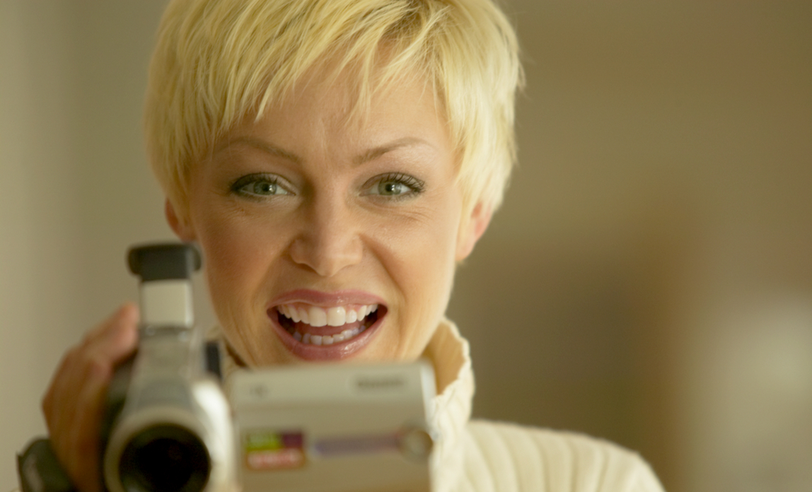 Woman using a video camera - Create an online video for your website