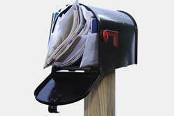 Open letter box filled with junk mail