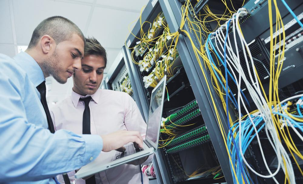 Two young IT engineers in a server room completing regular IT maintenance