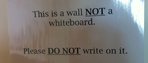 Sign saying 'this is a wall not a whiteboard'