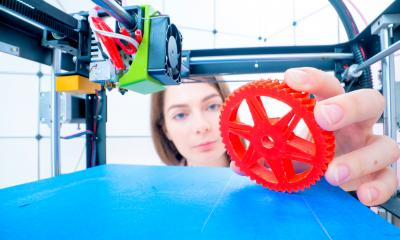 A young engineer works with a 3D printer to create a component or prototype - manufacturing concept.