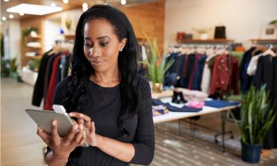 Retail assistant using tablet to check stock whilst in a clothes shop
