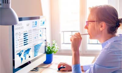 A businesswoman looks at business analytics on the computer screen