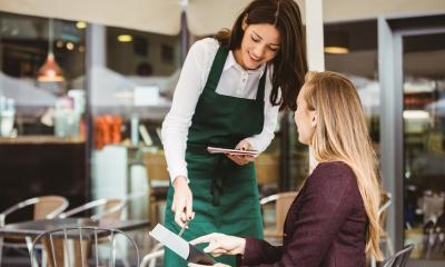 Business woman being served by a waitress in a cafe