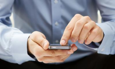 A business man keeps in touch with his colleagues using instant messaging on his mobile device