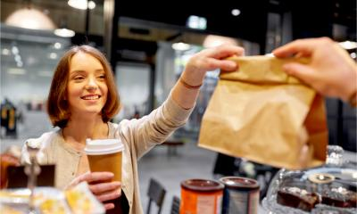 A happy female customer with coffee cup taking paper bag from man in a vegan cafe