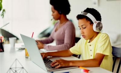 A boy completes his school work while his mother works remotely in the background