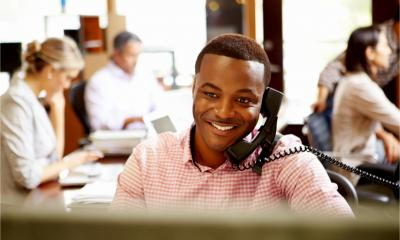 A smiling business man sits at his desk making a phone call to a client