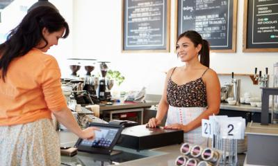 A female coffee shop owner smiles as a customer pays for her purchase using an ePOS terminal.