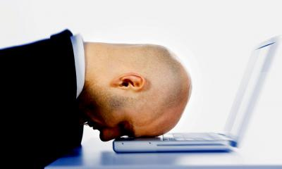 Bald man in a suit resting his head on his laptop having made a mistake