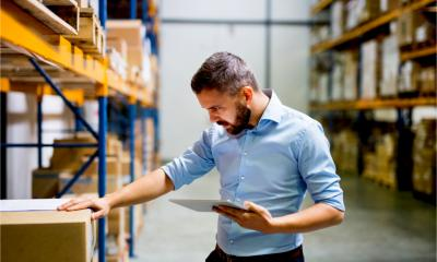 An attractive man checks his warehouse stock inventory