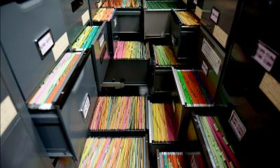 Multiple different filing cabinets with multicoloured documents in the drawers