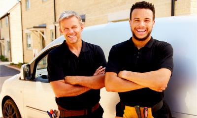 Portrait of a young and a middle-aged tradesman by their van