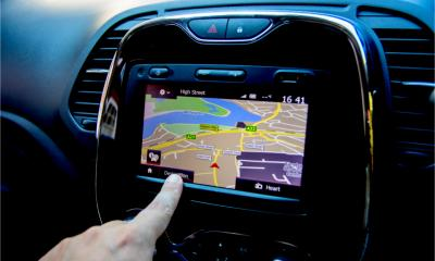 A hand is operating an in car GPS SATNav system