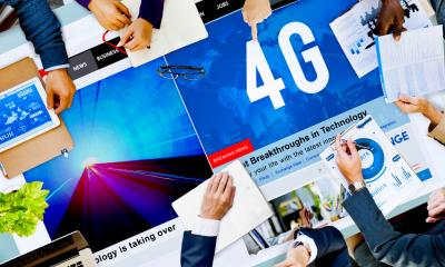 Table filled with superfast mobile internet posters with peoples hands holding various objects