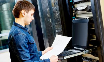 An IT provider wearing a denim shirt using a laptop next to a computer server