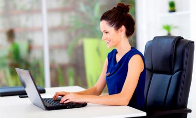 A lady with brunette hair sitting at a desk typing on a laptop