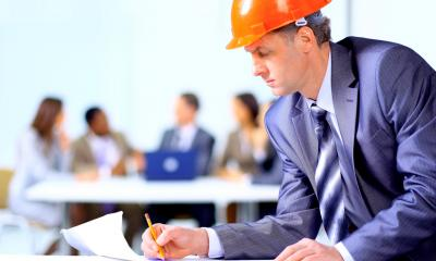 A man in a suit with a hard hat on writing on a piece of paper about IT health and safety FAQ