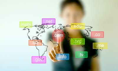 Multiple different domain name extensions on a blurred world map with a woman in the background