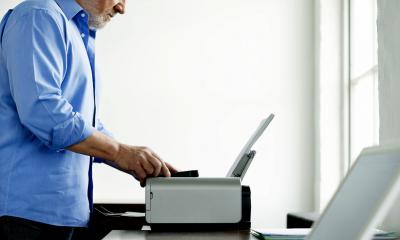 Bearded man in a blue shirt using a printer