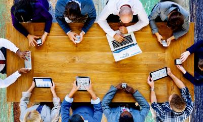 Overhead view of a team working on a range of IT devices