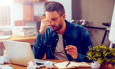 A man is feeling stressed as he can't find the documents he needs for work
