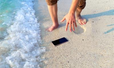 A man has dropped his phone on the beach and the waves are about to make it wet