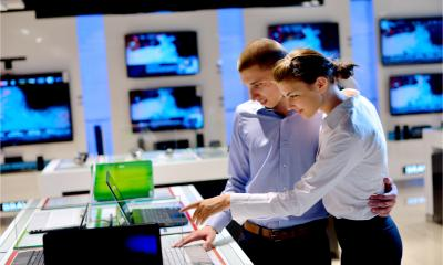 A young couple in an electronics store look at a new laptop on display