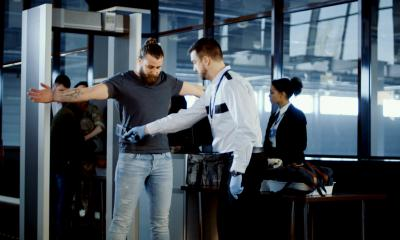 An airport security guard checks a passenger before he is allowed through the security gate