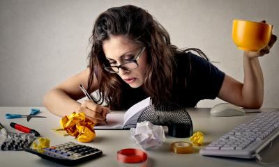 Woman wearing glasses sat at a messy desk holding a yellow mug in the air