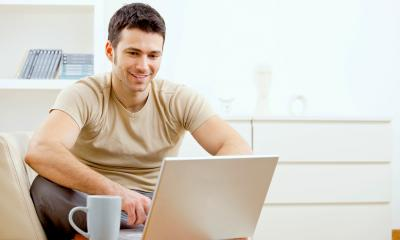 Man in a beige t-shirt working from home on his laptop with a mug beside him