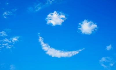 Smiling face formed from clouds in a bright blue sky