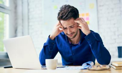 Man suffering from headache in the workplace