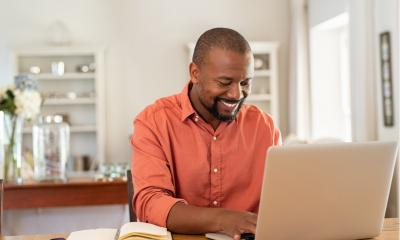 Smiling freelancer using laptop at home in living room