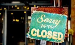 A closed sign in a shop window forced to close by local coronavirus restrictions