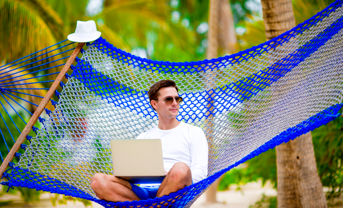 man using laptop on a hammock - ten apps to run your business from afar.