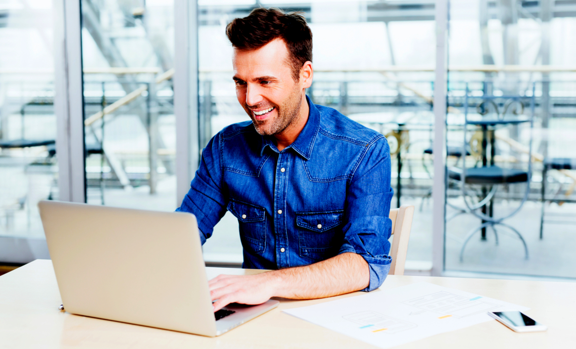 Man smiling using laptop - the five best freemium business services.